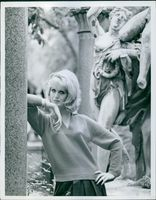 A woman striking a pose with a sculpture at the background, 1962.