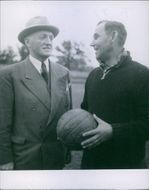 Two men standing and talking, holding football.