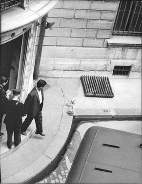 A man walking out of the building with two other men standing on the entrance door.