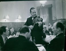 Man playing violin, other people enjoying in a restaurant in Sweden. Photo taken in 1964.