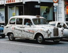 Taxis covered in newspaper articles.