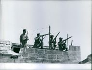 Soldiers standing on the roof, holding gun and targeting.