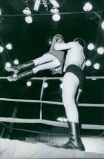 Man holding and lifting woman in the ring.