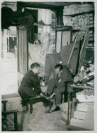 Mrs. Magnus with a man fitting a sandal in a shoe shop , devastated background caused by bomb explosion during war in England. 1940