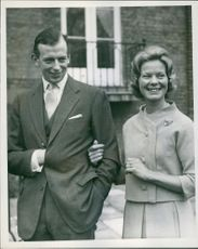 A nonchalant hand in coat pose for the Duke of Kent, as he walks with his fiancee, Katherine Worsley, in the gardens of his mother's London home at Kensington Palace. March 9, 1961.
