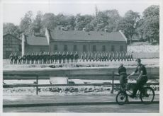 Man cycling and Labour Service men marching, Norway, 1940.