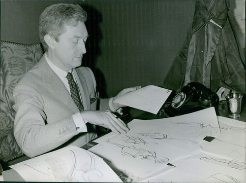 Man busy in his work, shuffling papers.
