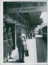 1945 C.S.M. First out in Today 's  Big Demobilisation. Major F.G. Packingston standing at the railway platform with other people and looking towards the camera.