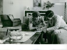King Hussein write notes while Princess Muna al-Hussein looks on.