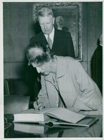 The King of Sweden King Kung Gustaf VI Adolf and Queen Louise visit Finland in 1952. The Queen writes his name in the Riksdaghuset visit book.