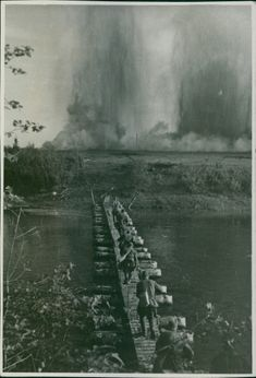 The theater of war. Red Army men crossing a river after restoring the bridge under the cover  of artillery fire. 1943