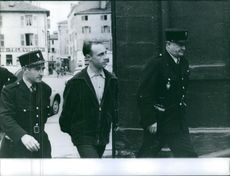 A man being escorted by two police officers.
