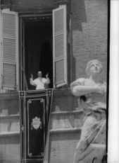 Pope Paul VI waving his hand by the window.