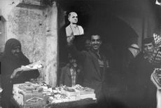 A man happily waves the photo of of Pope Paul VI to the photographer.