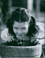 A young girl drinking in the fountain.