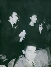 Man and woman standing in the theater, smoking cigarette.