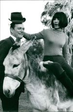 Eddie Constantine with a woman sitting on a donkey.