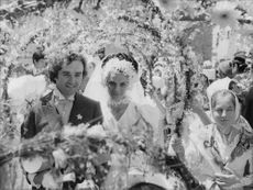 A man escorting a woman in formal attire on the street with a woman holding an arc decorated with flowers.