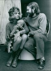 Serge & Christine Ghisoland siting together with baby.