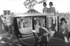 Queen Elizabeth II sitting in royal cart.