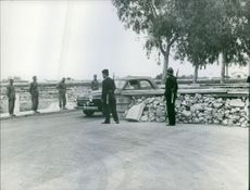Soldier standing beside a car in the village.