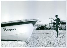 Mexican fisherman standing on the beach, holding net tied on boat in Baja, California.