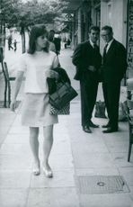 Two men looking at the woman who passed by, May 1967.