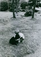 Carl XVI Gustaf of Sweden as a child, playing with his pet dog.