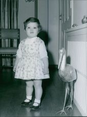 A little cute girl standing, looking towards the camera and smiling. 1967