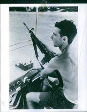 A man siting inside the vehicle, holding gun and patrolling.