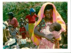 Rwanda war:a hutu mother comfort her child as she waits for a security.