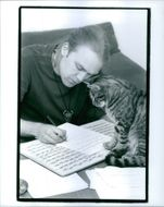 A man writing and a cute cat looking at him.