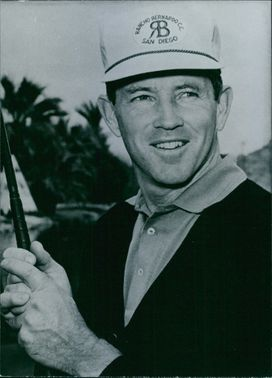 Gene Littler wearing a cap, smiling and holding a golf club.