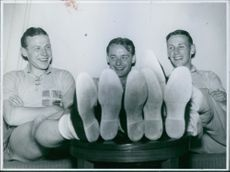 Three men sitting after their training in football.