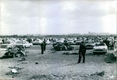 Policemen standing on an area where few wreck cars are parked, 1965.