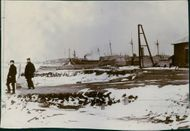 Soldiers standing on the frozen port and smoking cigar.  1904 The harbor at Nientsjvang march towards Yalu.