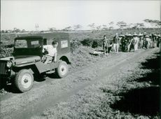 A jeep driver looking back towards the group of people,1964.
