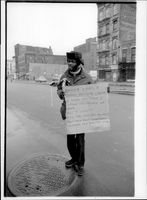 A homeless man with a poster