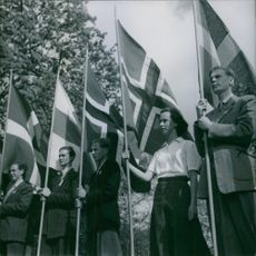 Men and women standing and holding their national flags. 1948