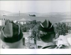 Two guys watching a chopper passing by a village. July 24, 1961.