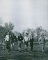 Footballers running together during the training.