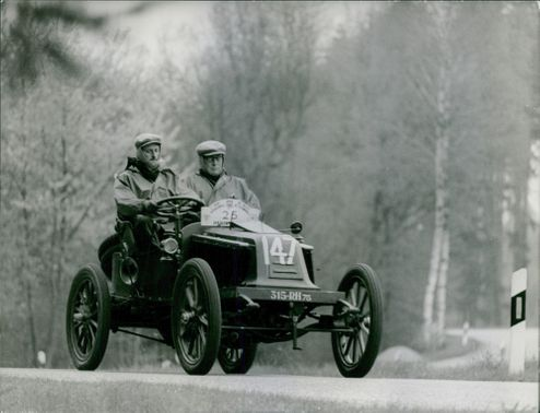 Two personnel driving/riding on a four-wheel vintage car. Car no. 147