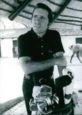 Gary Player poses beside a bag of golf clubs.