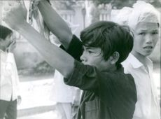 Protesters with plastics over their heads and a man raising both arms during their rally in the streets of Vietnam. 1966.