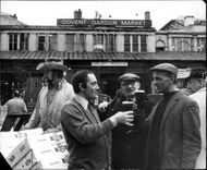 Last day of the old Covent Garden Market, some men drink beer outside the entrance
