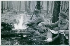 Soldiers sitting around  the fire during break time.