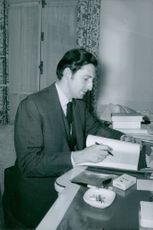A man reading a book and using a cigarette.
