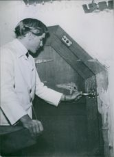 A man standing and opening a door.