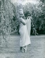 Marie-France Boyer posing in garden, covering herself with blanket.