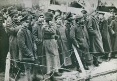 Soldiers gathered in the street in front of wire during World War I, 1936.